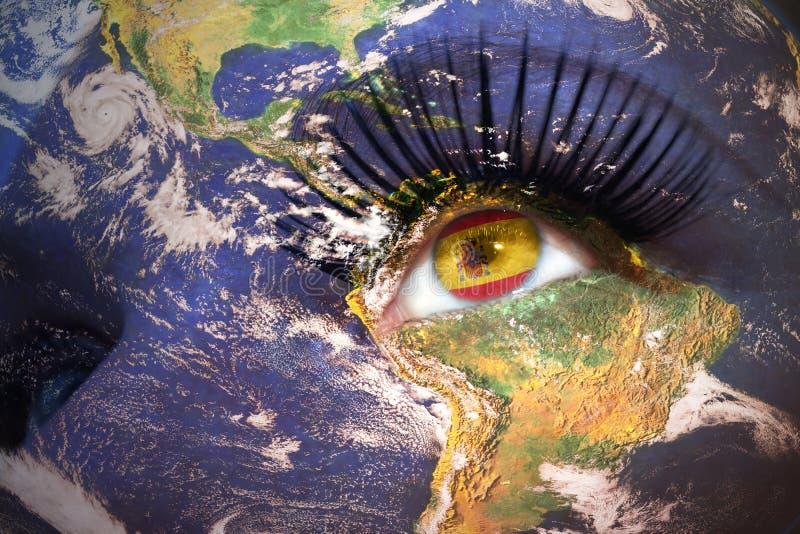 Visage du ` s de femme avec la texture de la terre de planète et drapeau espagnol à l'intérieur de l'oeil image libre de droits