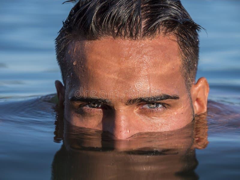 Visage du ` s de jeune homme demi dans l'eau dans la mer ou le lac images libres de droits