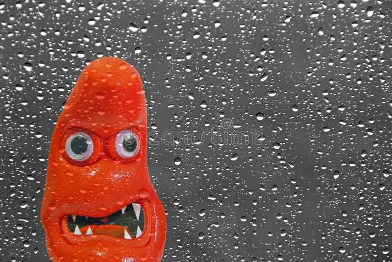 Visage effrayant de monstre à la fenêtre pluvieuse photographie stock