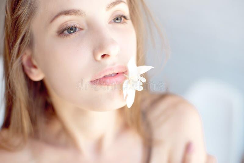 Visage en gros plan de belle jeune femme avec la peau de santé et de fleur dans la bouche photos stock