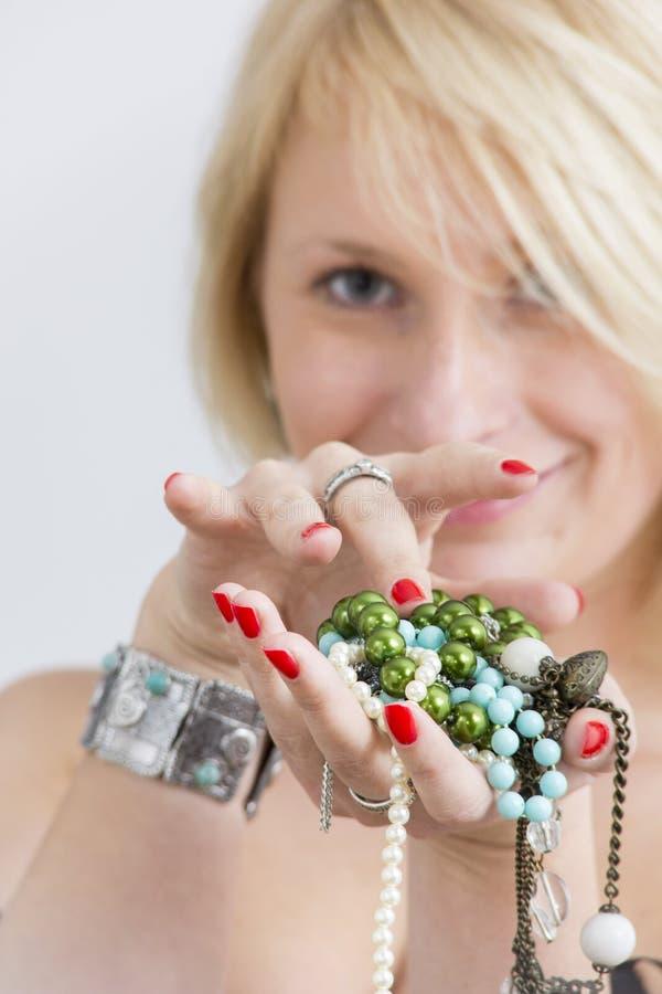 Visage et mains de femme avec les clous et les bijoux rouges image libre de droits