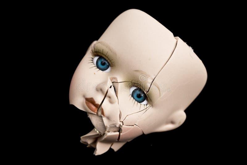 Visage et tête cassés de poupée sur le fond noir photographie stock