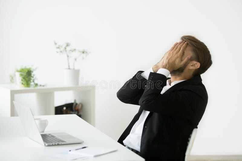 Visage faillite soumis à une contrainte affolé de bâche d'homme d'affaires avec la main images stock
