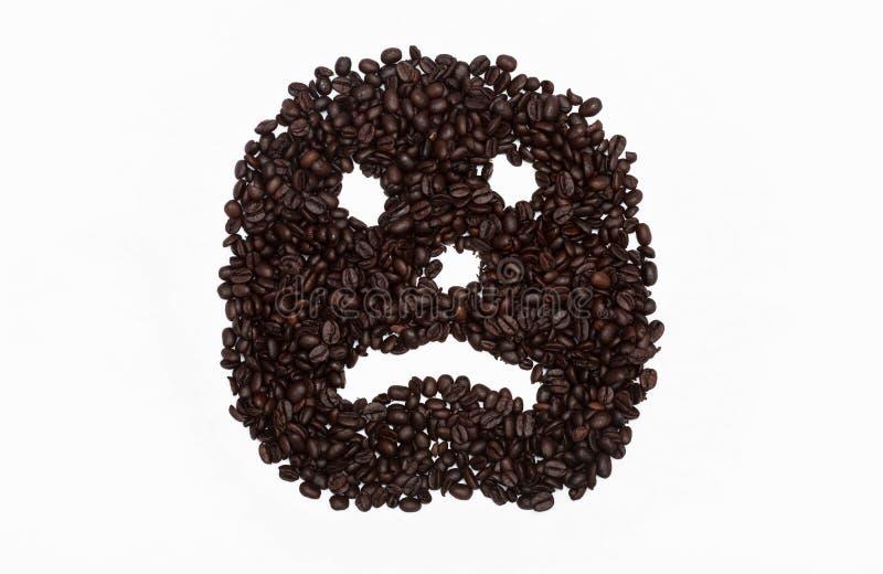 Visage grincheux ou triste en grains de café photographie stock