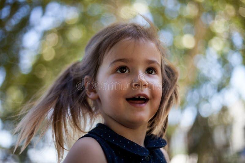 Visage heureux d'enfant avec les cheveux blonds, les eys bruns et le fond de bokeh photos stock