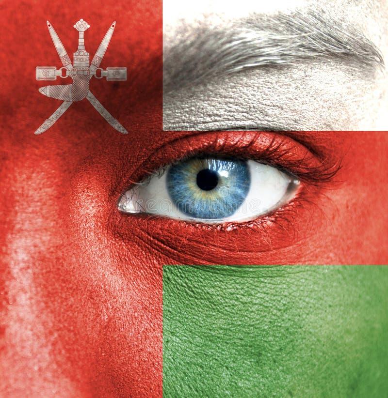 Visage humain peint avec le drapeau de l'Oman photo stock