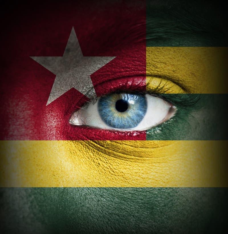 Visage humain peint avec le drapeau du Togo photographie stock