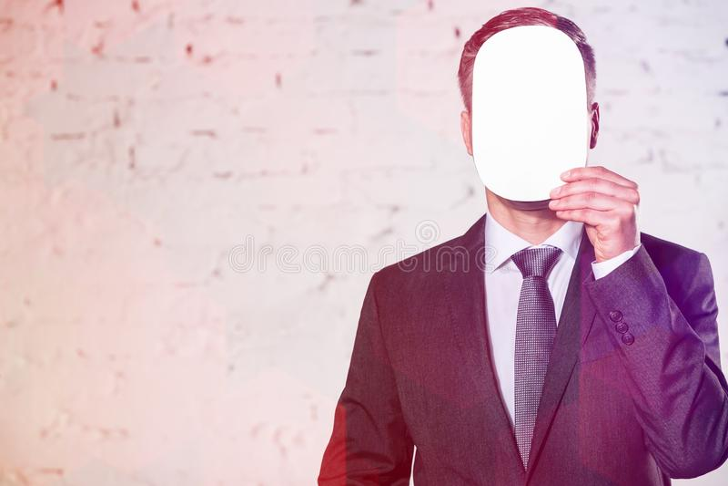 Visage m?r de b?che d'homme d'affaires avec le papier blanc contre le mur de briques blanc au bureau images libres de droits