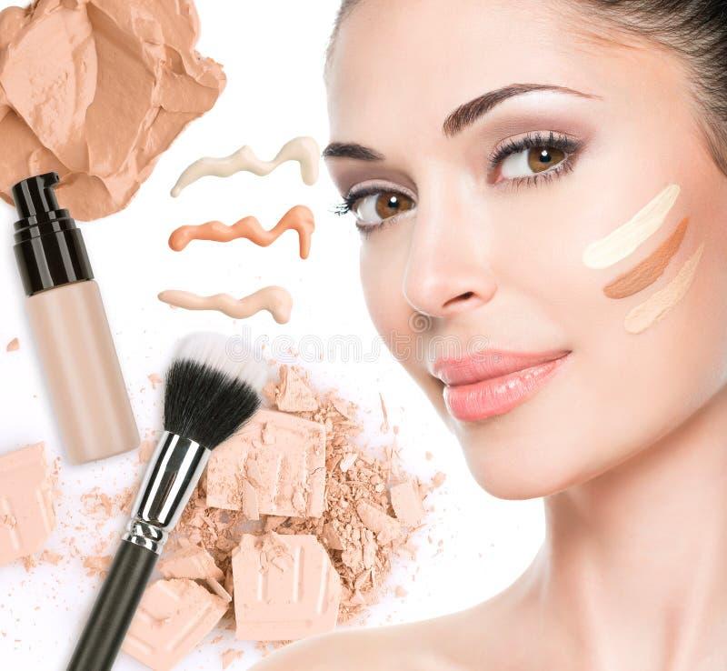 Visage modèle de belle femme avec la base sur la peau images stock