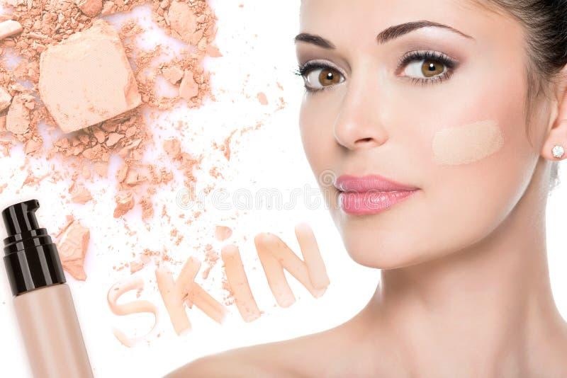 Visage modèle de belle femme avec la base sur la peau photos stock