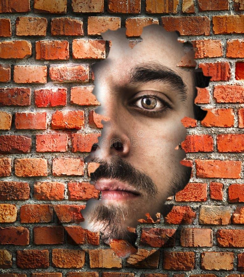 Visage remarquant par un mur photographie stock libre de droits