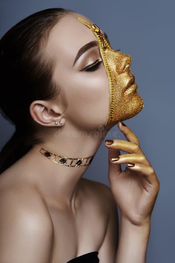 Visage sinistre créatif de maquillage d'habillement d'or de tirette de couleur de fille sur la peau Cosmétiques créatifs et soins photo stock