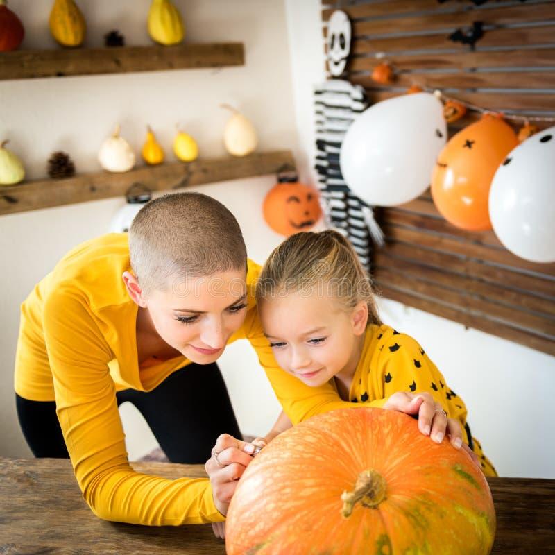Visage souriant de dessin de mère et de fille sur un grand potiron de Halloween Famille décorant le potiron image stock
