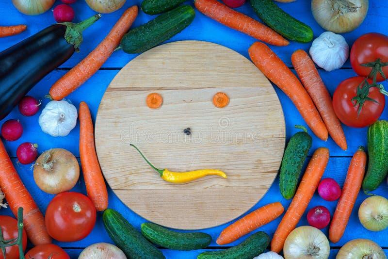 Visage souriant fait à partir des légumes parmi les légumes frais image libre de droits