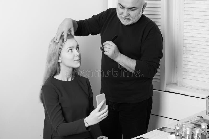 visage Weblog, blogging Bemannen Sie das Anwenden des Pulvers auf Mädchengesichtshaut mit Make-upbürste lizenzfreies stockfoto