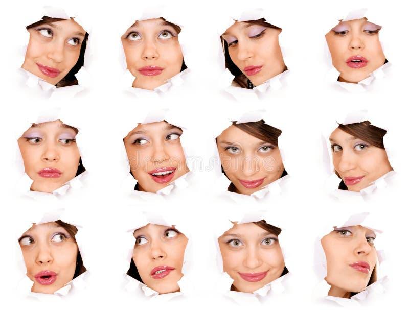 Visages de la fille dans un trou de papier photos stock