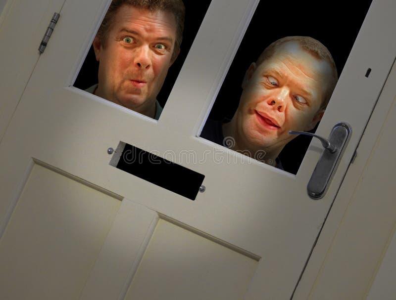 Visages fous scrutant par la porte photo stock