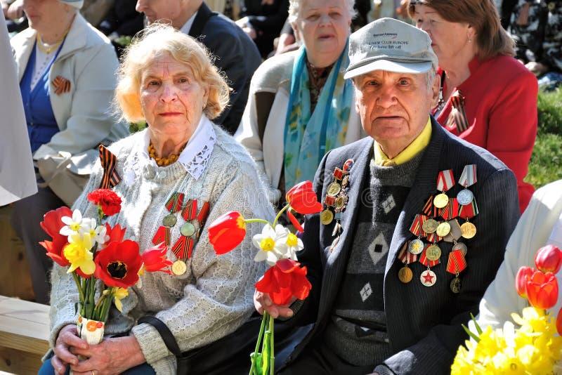 VISAGINAS, LITUANIA - 9 DE MAYO DE 2011: Veteranos del abuela y de abuelo de la gran Segunda Guerra Mundial patriótica con las fl imagen de archivo