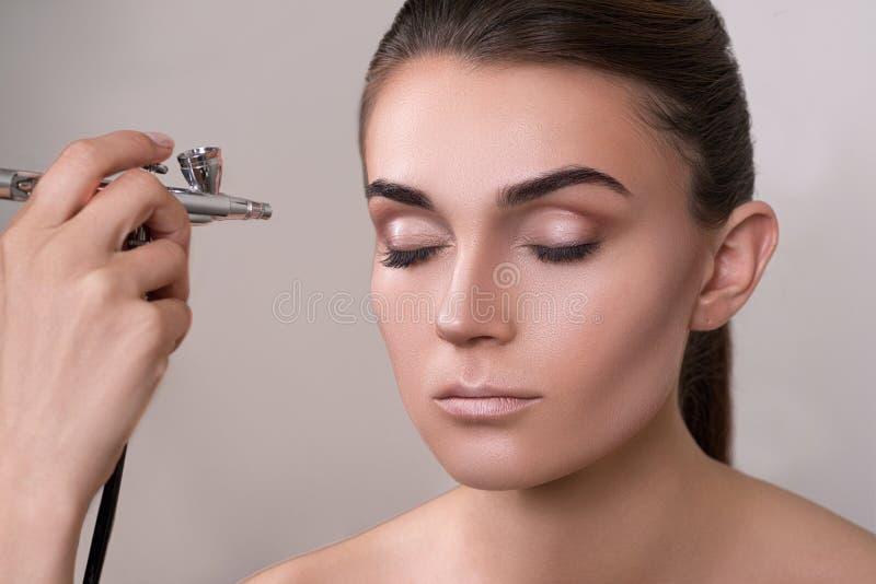 Visagist faisant le maquillage pour le modèle avec le météorographe, d'isolement sur le gris Fond avec le météorographe de partic image libre de droits