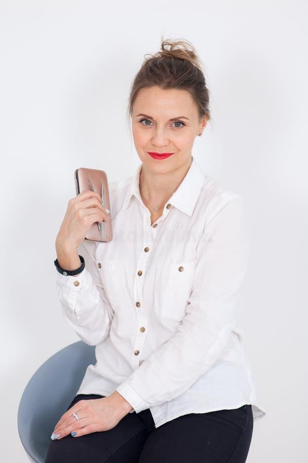 Visagist femelle mignon avec les cheveux blonds et les lèvres rouges sensuelles tient des instruments pour des traitements de bea photo libre de droits