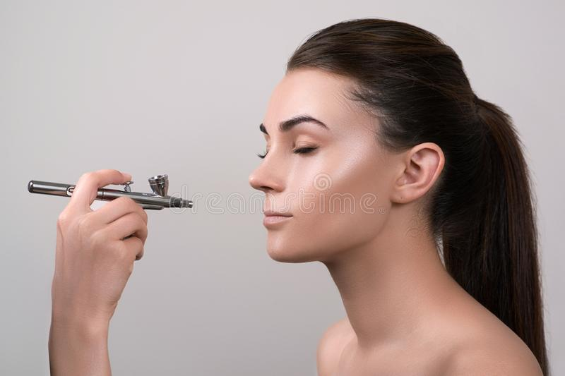 Visagist making makeup for model with aerograph, isolated on grey. Background with hand holding aerograph. Visagist using aerograp. H. Professional makeup for royalty free stock photo