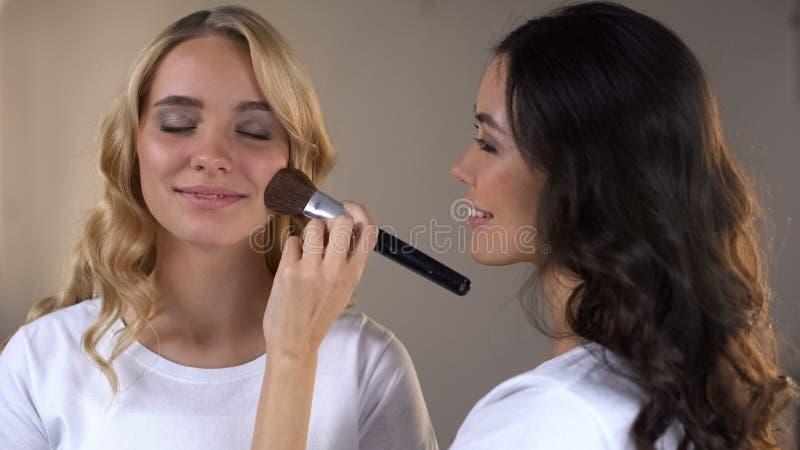 Visagiste applying evening make up on womans face, beauty tips, workshop stock photography