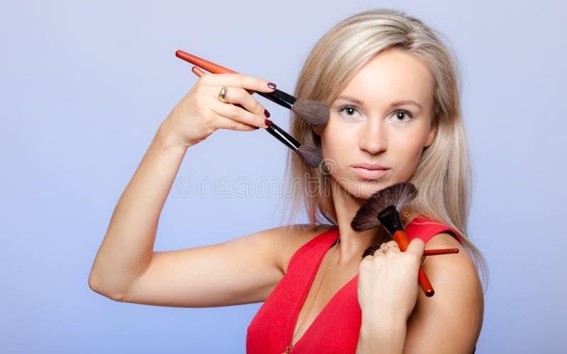 Visagiste biondo dello stilista della ragazza che tiene le spazzole professionali di trucco immagini stock