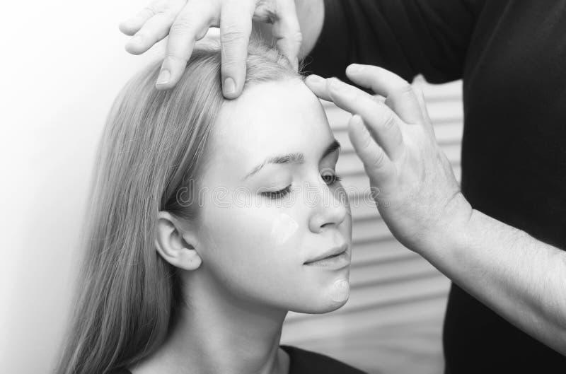 Visagiste entrega a aplicação do ocultador na pele da cara da mulher imagem de stock royalty free