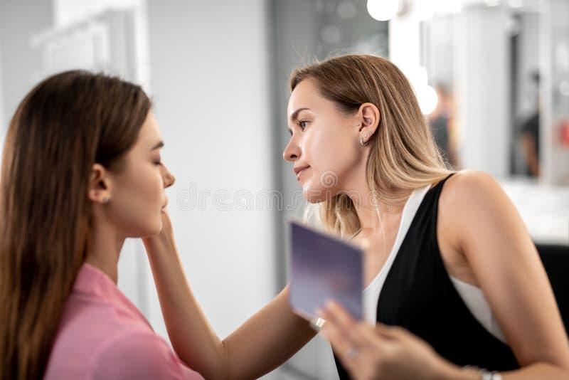 Visagiste gör makeup till den nätta flickan fotografering för bildbyråer