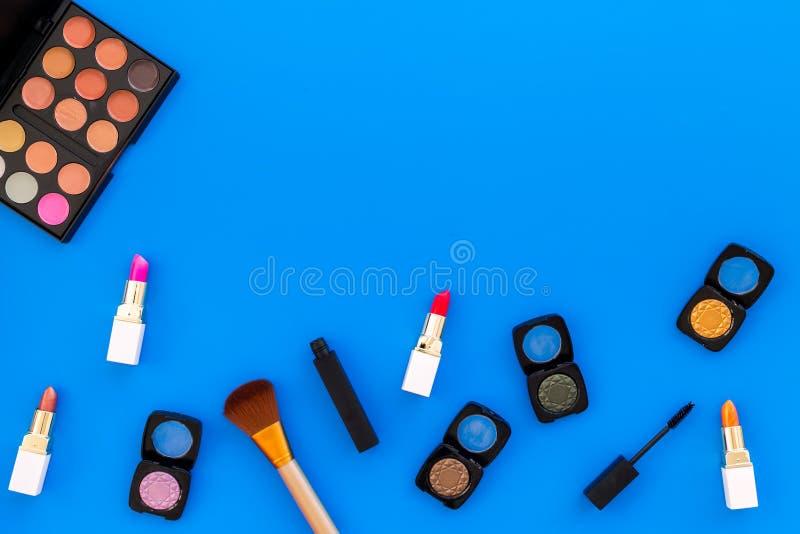Visagiste-Schreibtisch mit dekorativen Kosmetik: Lidschatten, Lippenstift, Draufsichtraum des Hintergrundes der Bürste blauer für stockfoto