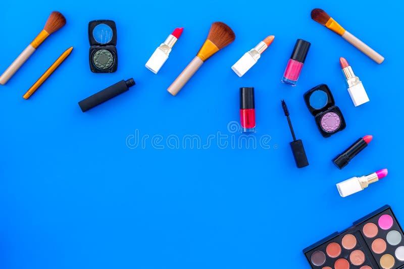 Visagiste-Schreibtisch mit dekorativen Kosmetik: Lidschatten, Lippenstift, Draufsichtraum des Hintergrundes der Bürste blauer für lizenzfreie stockbilder