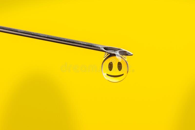 Visare med en droppe och ett leende på gul bakgrund Droger från injektionssprutan royaltyfri foto