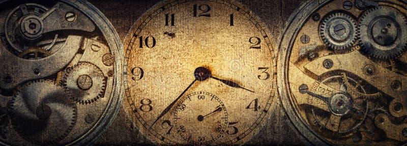 Visartavlorna av de gamla antika klassiska klockorna p? en tappningpappersbakgrund Begrepp av tid, historia, vetenskap, minne, in arkivfoton