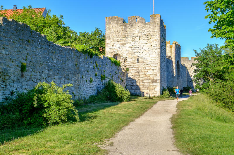 Visby city wall. Visby, Sweden - June 11, 2014: A woman runs outside the medieval city wall in Visby. The famous city wall from the 13th century is a Unesco stock photography