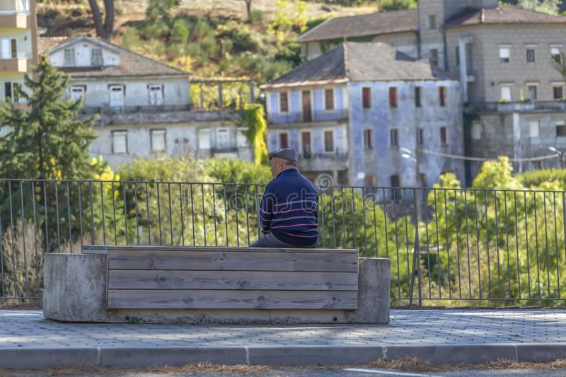 Back view of senior man relaxing sitting on a concrete and wooden bench on the pedestrian edge of a sidewalk road stock photo