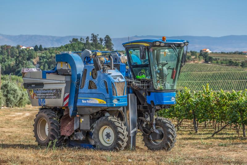 View of a grape harvesting machine on agricultural fields with vineyards royalty free stock image