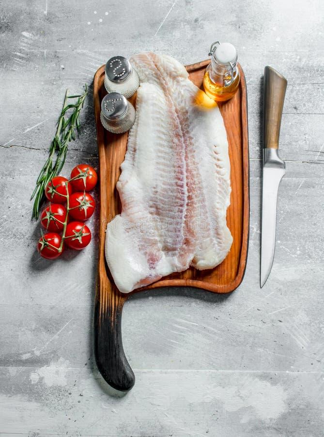 Visfilet op een knipselraad met een mes, kruiden, olie en tomaten op een tak stock foto