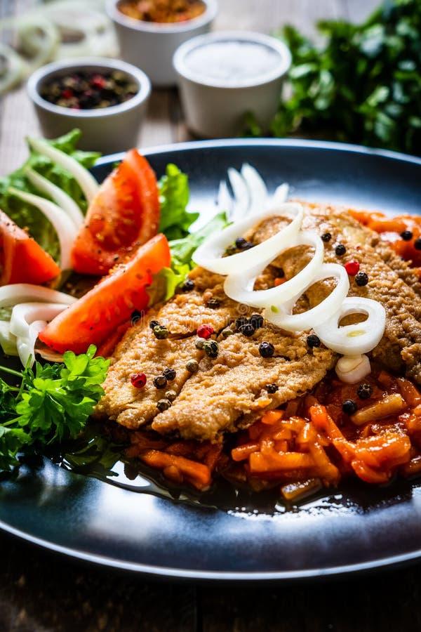 Visgerecht - gefrituurde visfilet op plantaardige saus op houten tafel stock foto's