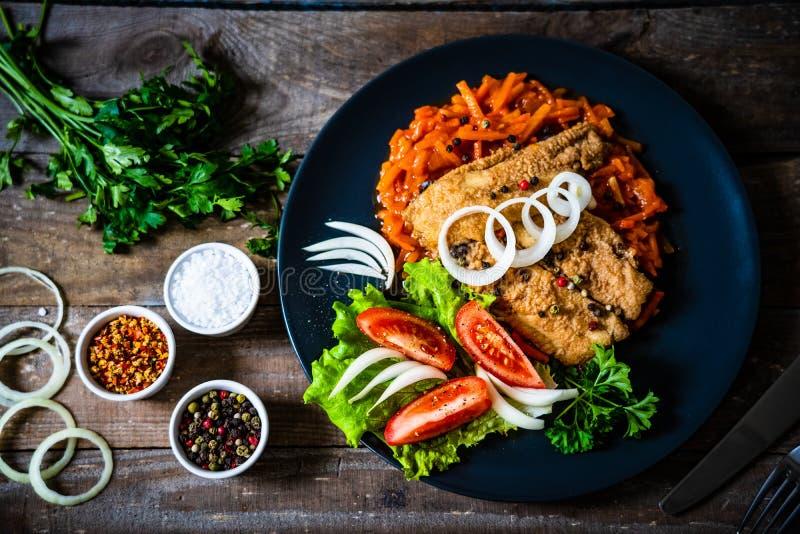 Visgerecht - gefrituurde visfilet op plantaardige saus op houten tafel royalty-vrije stock afbeelding