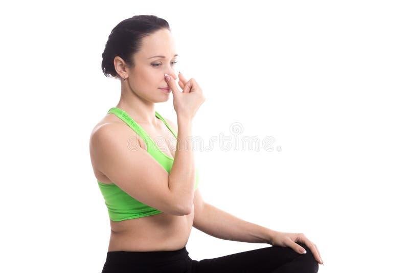 Vishnu Mudra in hatha yoga Alternate Nostril Breathing. Vishnu Mudra for hatha yoga nadi Shodhan pranayama technique, serene girl practicing yoga, meditating royalty free stock image