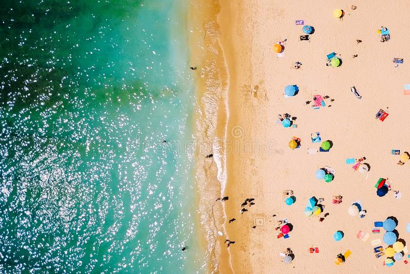 Visión aérea desde el abejón del vuelo de la muchedumbre de la gente que se relaja en la playa imagenes de archivo