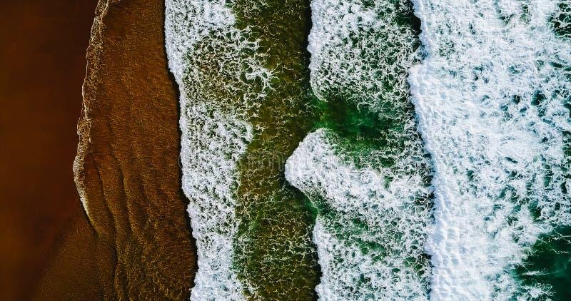 Visión aérea desde el abejón del vuelo de las olas oceánicas que machacan en la playa imágenes de archivo libres de regalías