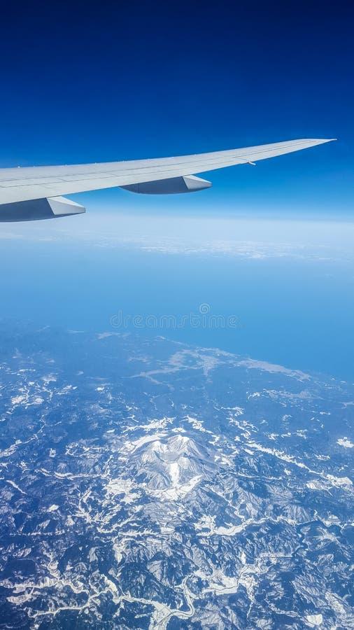 Visión aérea desde la ventana del aeroplano sobre Japón con el ala del ` s del aeroplano imagen de archivo