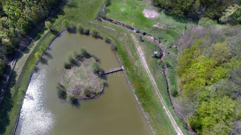 Visión aérea sobre un pequeño lago con una isla formada hermosa en Sarlos, Hungría fotos de archivo