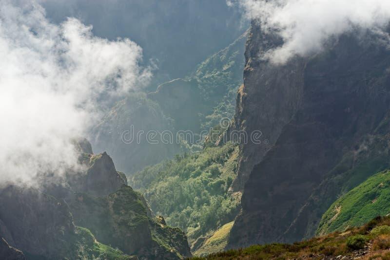 Visión abajo desde el pico de montaña en un valle en el distante imagen de archivo libre de regalías