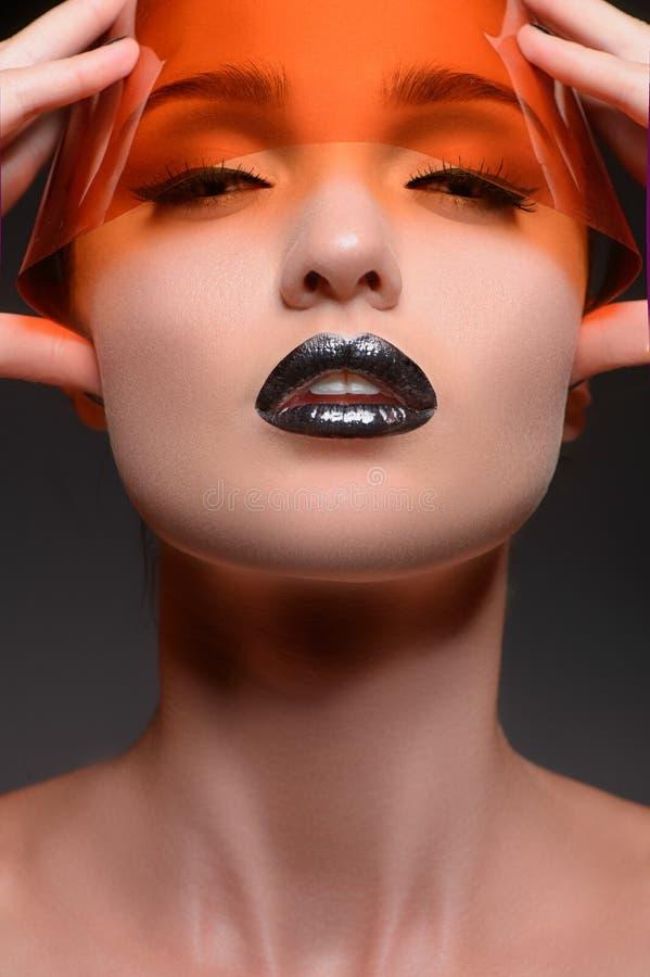 Visión anaranjada. El retrato de mujeres hermosas con los ojos cerrados se sostiene imágenes de archivo libres de regalías