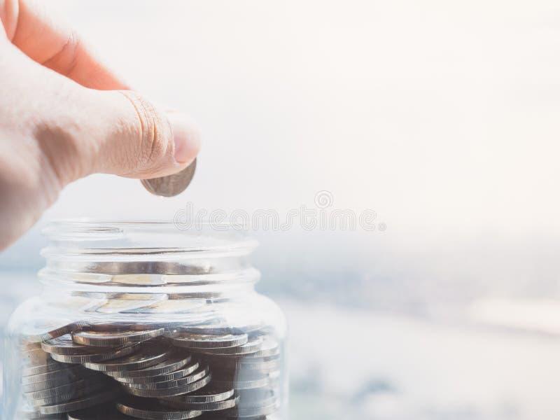 Visión ascendente cercana en el lado de la mano que sostiene una moneda para poner el dinero en una botella de cristal fotos de archivo