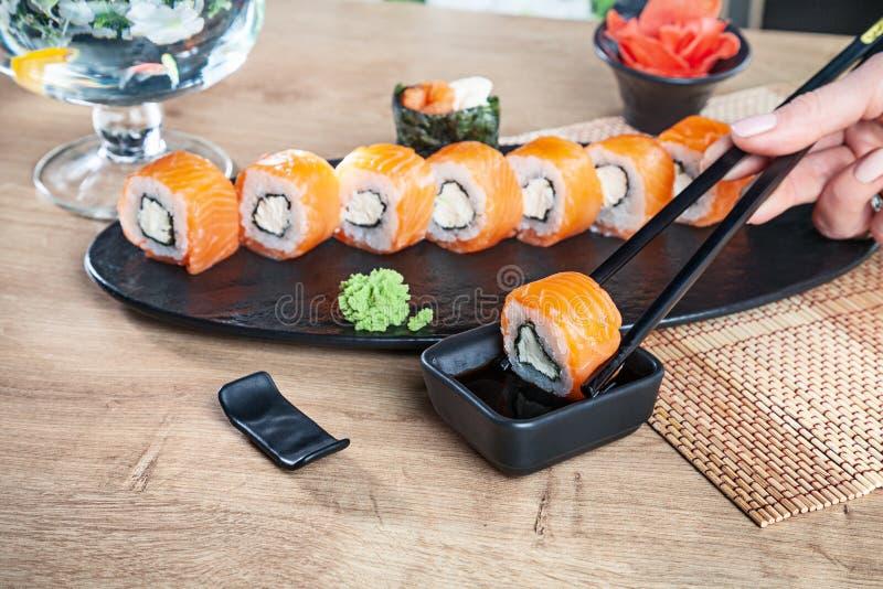 Visión ascendente cercana a mano que sostiene los palillos y el sushi de la clavada en salsa de soja Rollo de California con los  fotografía de archivo libre de regalías