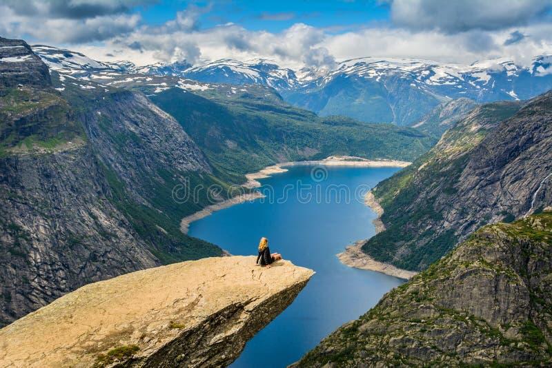 Visión asombrosa con Trolltunga y una muchacha que se sienta en él noruega fotos de archivo libres de regalías