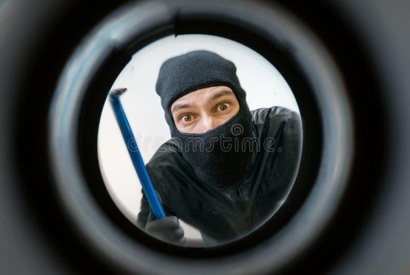 Visión con mirilla El ladrón o el ladrón enmascarado con el pasamontañas está detrás de la puerta foto de archivo libre de regalías